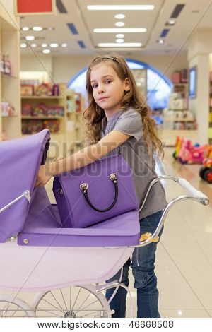 Modern little girl in a toy store purchased a buggy and handbag