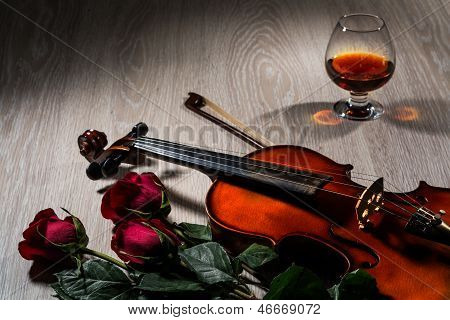 Violin, rose, glass of champagne and music books