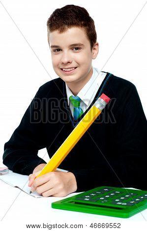 Boy Doing Homework With Calculator Beside Him