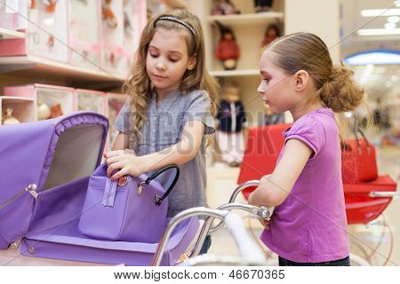 Two girls in a toy store with dolls purchased a buggy and handbag, focus on right girl