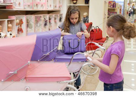Two girls in a toy store purchased a buggy and handbag