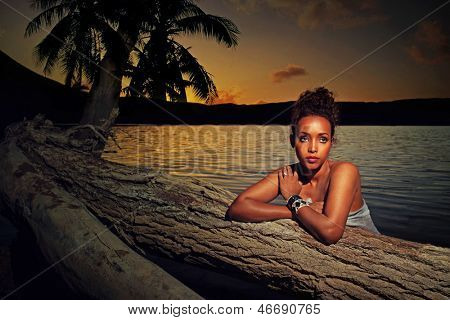Mystical portrait of a beautiful young African girl at sunset leaning on the trunk of a palm tree with an ocean backdrop and soft shadowed lighting