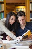 stock photo of helping others  - Two students at a table in a library learning and helping each other - JPG