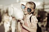 foto of candy cotton  - Girl eating cotton candy - JPG