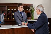 Smiling receptionist behind counter in hotel giving key card to senior guest