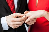 stock photo of fiance  - picture of man putting  wedding ring on woman hand - JPG