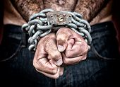 image of slaves  - Dramatic detail of the chained hands of an adult man  - JPG