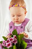 stock photo of pinafore  - Portrait of little girl dressed in violet pinafore dress with headband in form of chaplet on her head with bunch 0f flowers - JPG