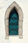 pic of ironworker  - Green medieval window with ornate ironwork on a white washed wall - JPG