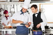 image of waiter  - Chef and waiter using digital tablet with female chef working in restaurant kitchen - JPG