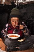 picture of beggar  - Poor beggar child eating charity food on the street sitting on cardboard plank - JPG