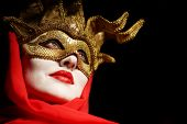 closeup portrait of sexy woman in golden theater mask for desire concept