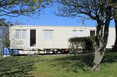 pic of trailer park  - Scenic view of static caravan on trailer park under trees - JPG