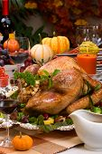 stock photo of turkey dinner  - Garnished roasted turkey on holiday decorated table with pumpkins and glasses of red wine - JPG