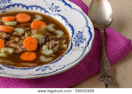Chicken Soup On Old Vintage Table With Carrots And Selery On Top And Silver Spoon On The Side