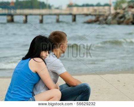 Loving Young Couple Is Sitting Near The Sea