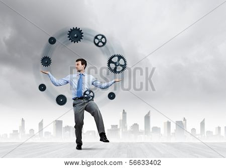 Handsome businessman juggling with gears against city background