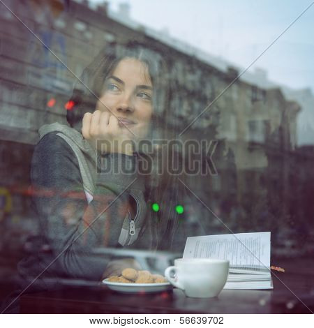 Young woman drinking coffee and reading book sitting indoor in urban cafe. Cafe city lifestyle. Casual portrait of teenager girl. Toned.