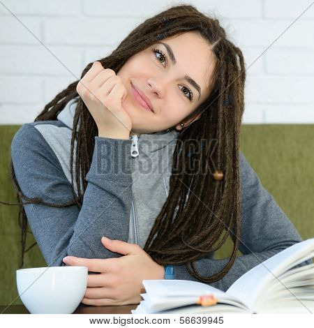 Young woman drinking coffee and reading book sitting indoor in urban cafe. Cafe city lifestyle. Casual portrait of teenager girl.
