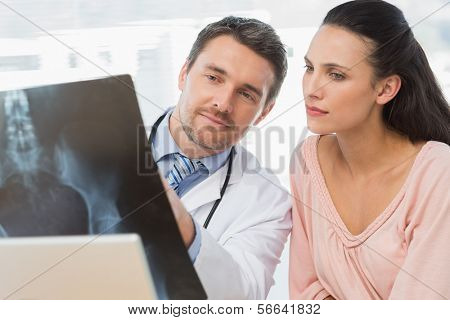 Male doctor explaining x-ray report to a patient in medical office