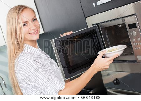 Jovem mulher aquece a comida no microondas