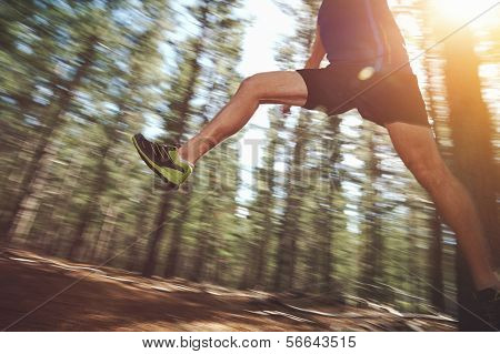 Runner jumping on trail run in forest for marathon fitness