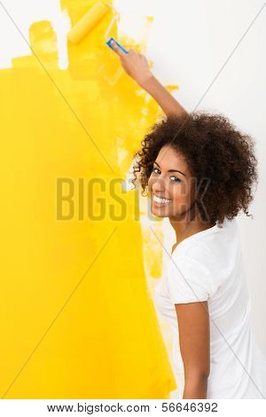 Happy Young Woman Painting A Wall Orange