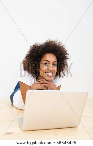 Happy Woman Lying On The Floor With A Laptop