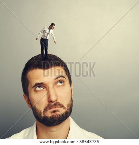 amazed man looking up at small man on the head