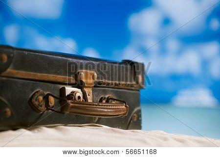 old retro antique suitcase on beach, sea and sky backgound