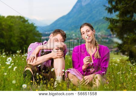 Couple in traditional dress sitting in the meadow with mountain panorama having some issues