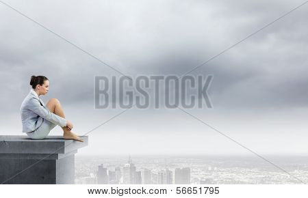 Image of young attractive businesswoman sitting alone atop of building