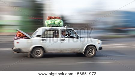 Old Car Loaded With Cabbage And Carrots Rides Through The City Streets