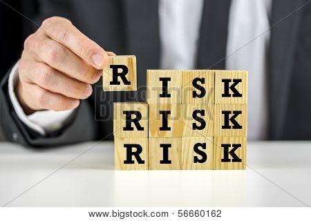 Man Stacking Wooden Risk Blocks