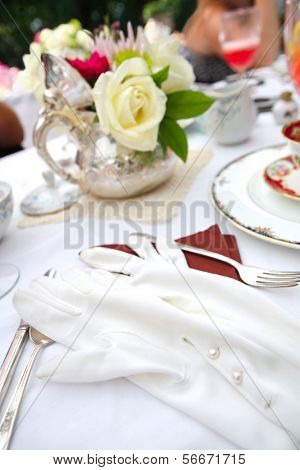 Table setting with vintage gloves at a tea party, shallow focus