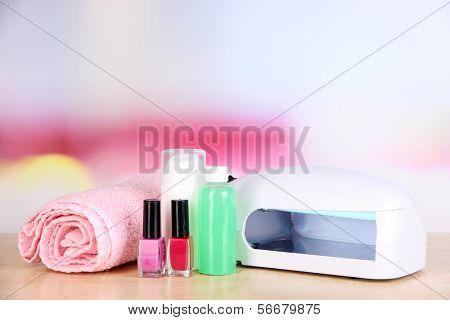 Lámpara para uñas y accesorios para manicura en mesa sobre fondo brillante