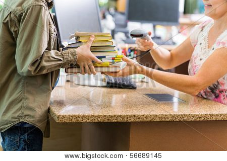 Midsection of schoolboy holding books while librarian scanning them at checkout counter in library