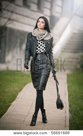 Attractive young woman in a winter fashion shot. Beautiful fashionable young girl in black leather