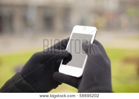 Man with smart phone in hand, glove, blurred background