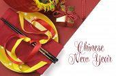 foto of chopsticks  - Happy Chinese New Year dining table place setting with red and gold decorations and chopsticks with greeting message text - JPG