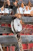 stock photo of pulley  - An Antique Rope and Pulley Hanging from an Old Weathered Fence - JPG
