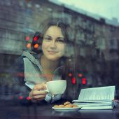 foto of dreadlock  - Young woman drinking coffee and reading book sitting indoor in urban cafe - JPG
