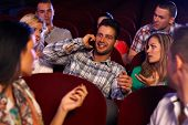 image of cinema auditorium  - Confident young man talking on mobilephone in cinema - JPG