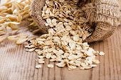 pic of roughage  - Oat flakes spilling from the burlap bag on wooden table - JPG
