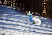 pic of snowboarding  - Snowboarder doing a toe side carve with deep blue sky in background - JPG