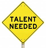 image of competing  - Talent Needed yellow road warning sign to illustrate a need to find skilled people or talented workers for a job or task - JPG