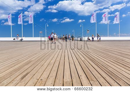 SOPOT, POLAND - 7 JUNE: People on Sopot molo at Baltic Sea, 7 June 2014. Sopot is major health and tourist resort destination and this pier with 511.5 meters long is the longest wooden pier in Europe.
