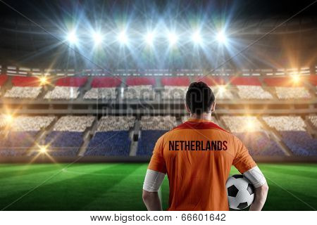 Netherlands football player holding ball against stadium full of netherlands football fans