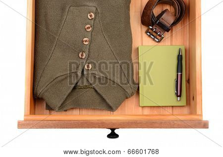 High angle shot of a sweater, belt, book and pen in a dresser drawer. Horizontal format isolated on white.
