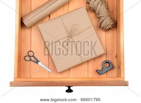 High angle shot of a wrapped package wrapped in plain brown paper in a desk drawer. The wooden drawer also contains scissors, twine, tape and a roll of brown paper.